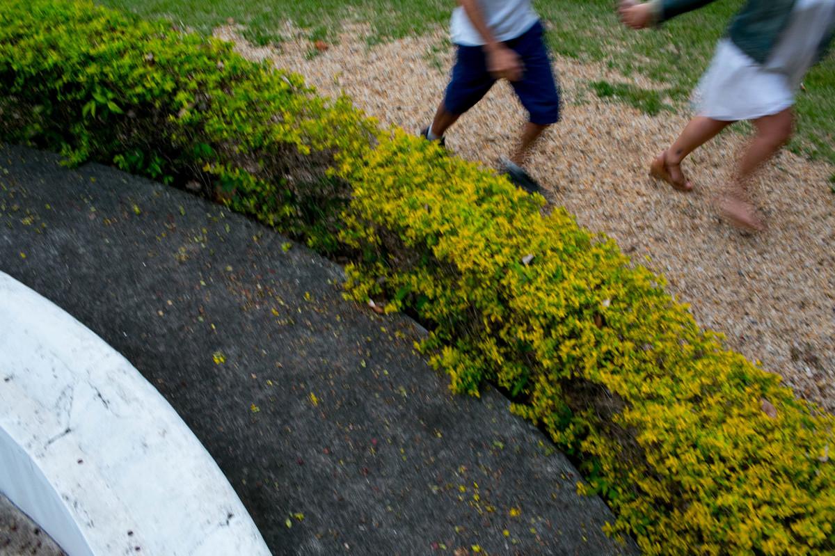 foto do detalhe das pernas em movimento, a foto tem um angulo diagonal, que deixa a foto muito equilibrada, alem da textura das pedras, do verde da grama e do cinza do asfalto.