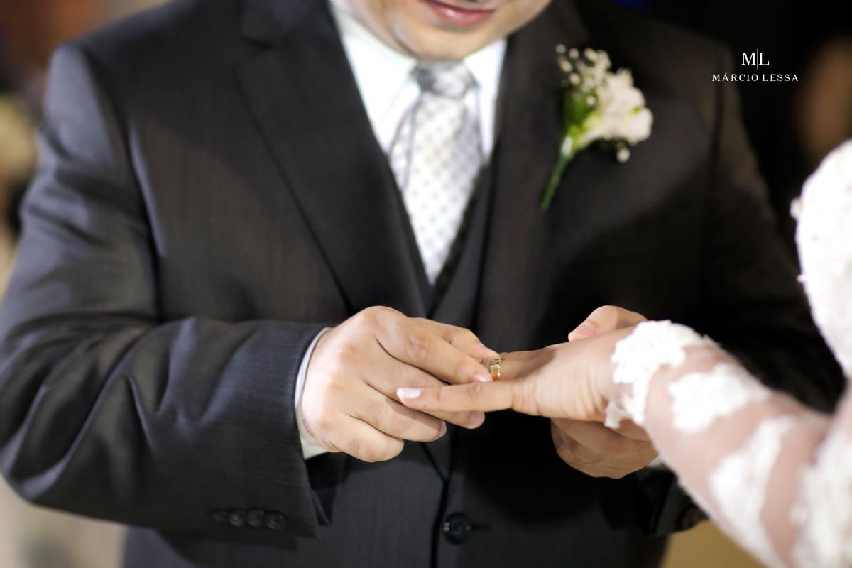 O noivo colocando a aliança no dedo da noiva