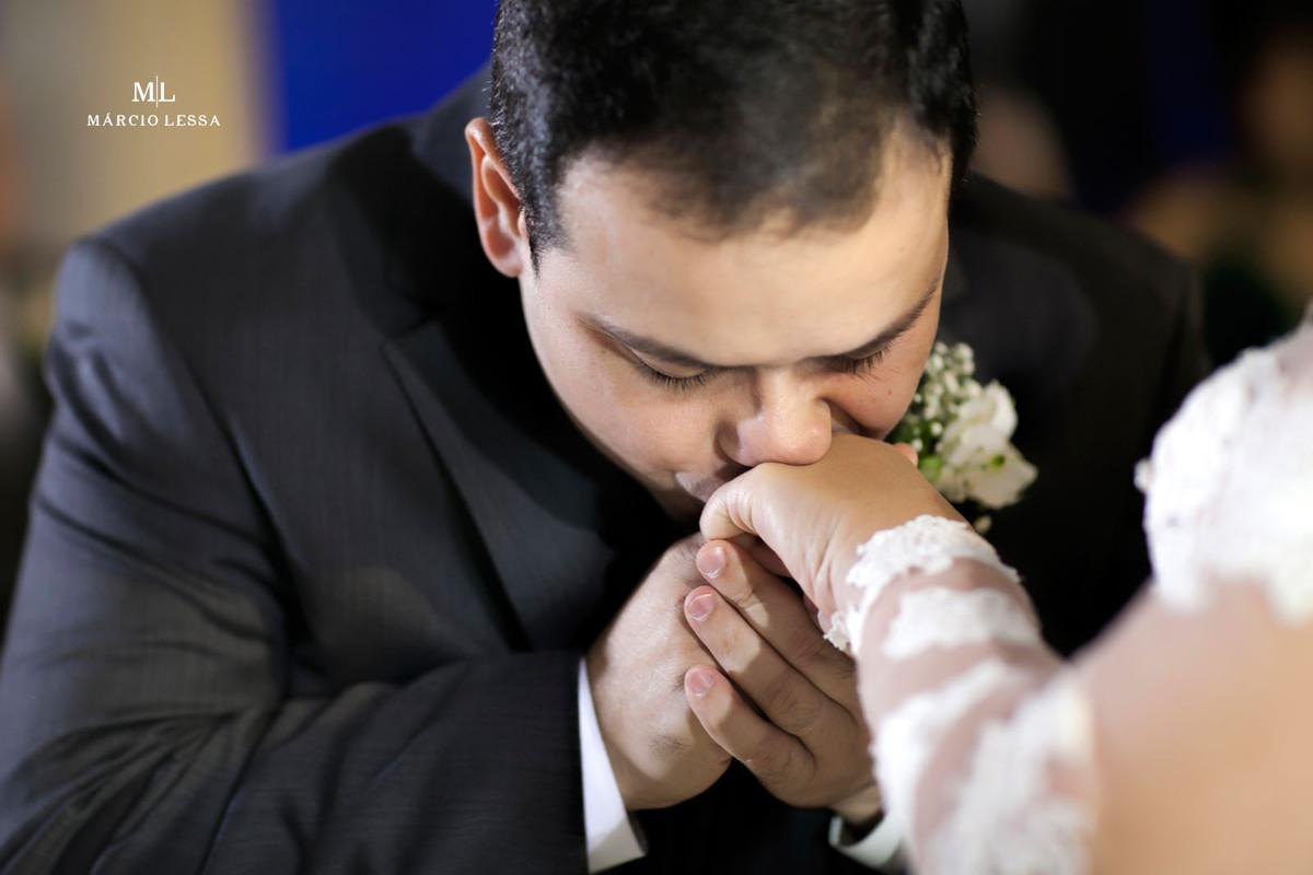 O noivo beijando a mão da noiva