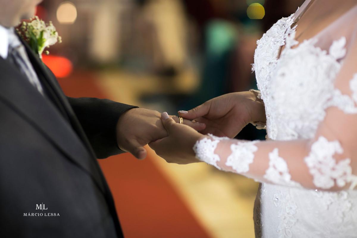 A noiva colocando a aliança no dedo do noivo
