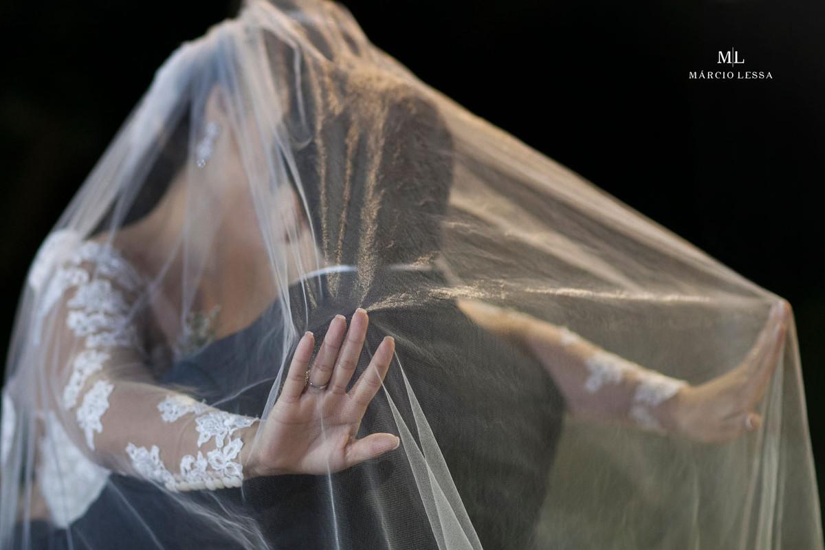 O beijo dos noivos sob o véu do lindo vestido de noiva