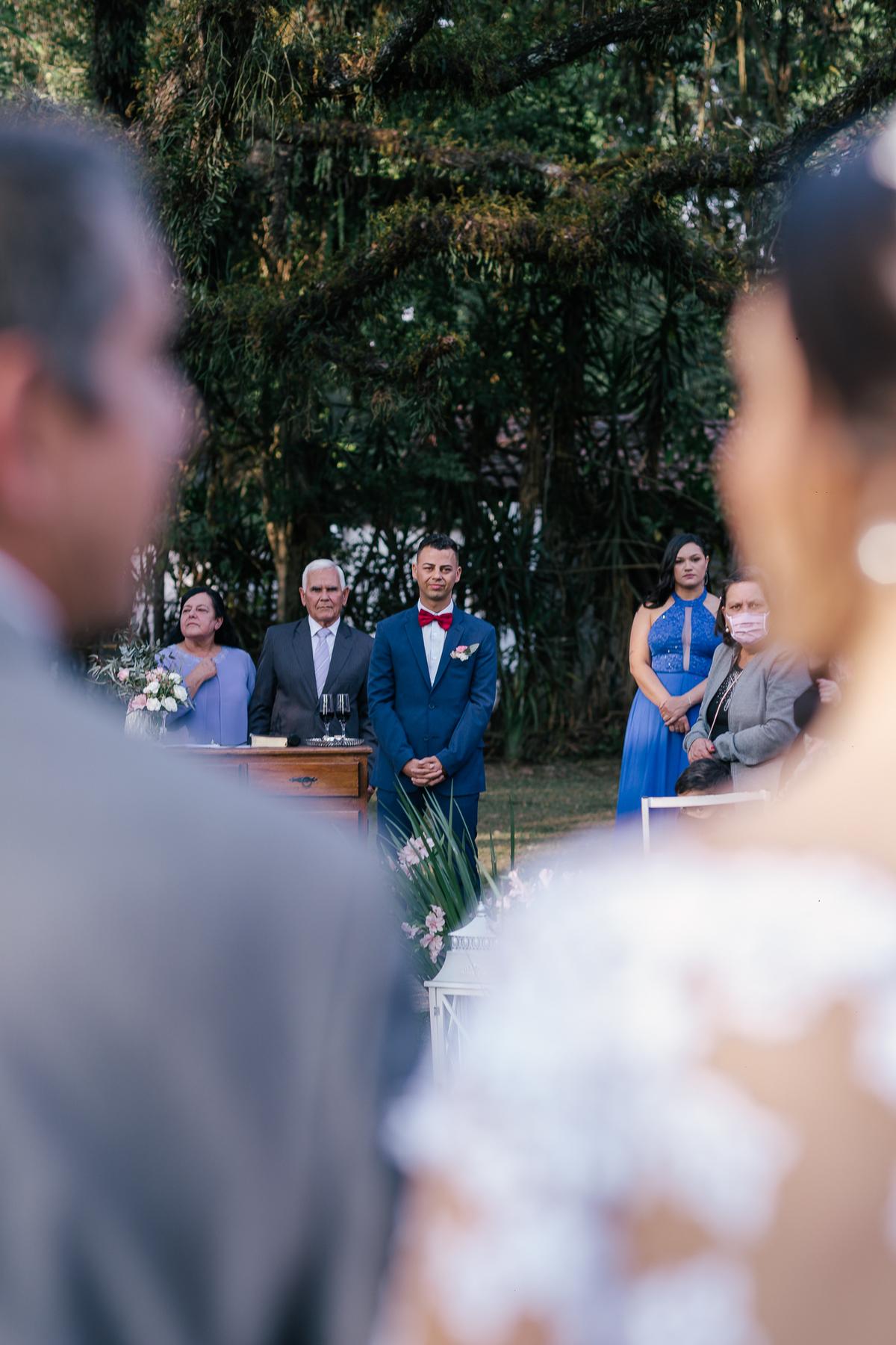 noiva na entrada da cerimonia com o noivo olhado ao fundo