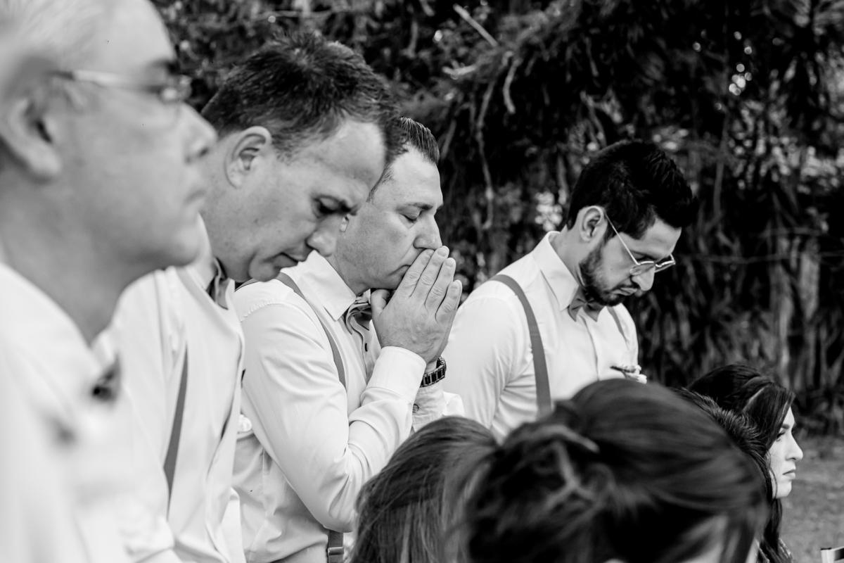 padrinho orando pelo casal durante cerimonia de casamento ʋ