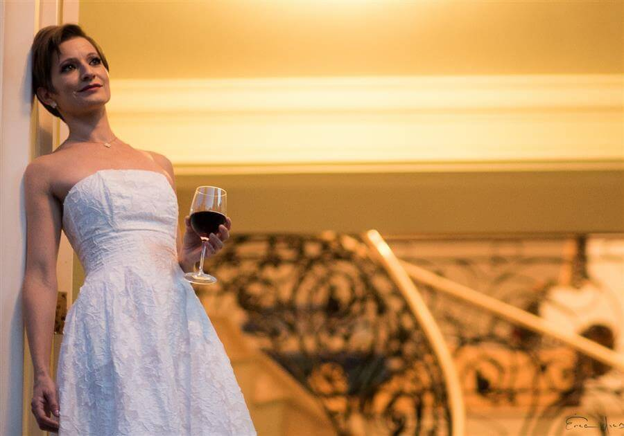 Um ar de nostalgia e sensualidade compõe esta fotografia. A escada com tons de dourado e a mulher com vestido branco segurando a taça de vinho traz sensualidade a esta composição.