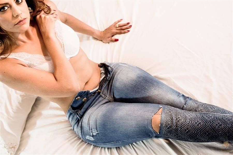 Ensaio casual com mulher vestida de calça jeans e sutiã.