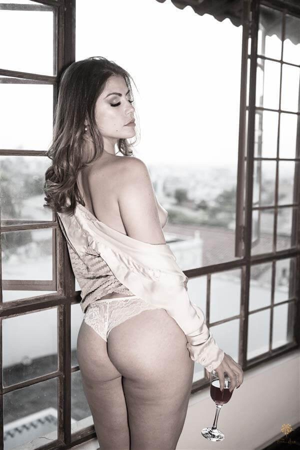 Nada mais sensual que uma mulher de lingerie e uma taça de vinho, esperando o pôr-do-sol na janela do estúdio Érica Dias.