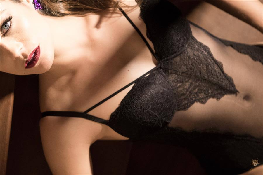 Foto sensual do Book Boudoir desta linda mulher, deitada na escada do estúdio, vestida de lingerie preta.