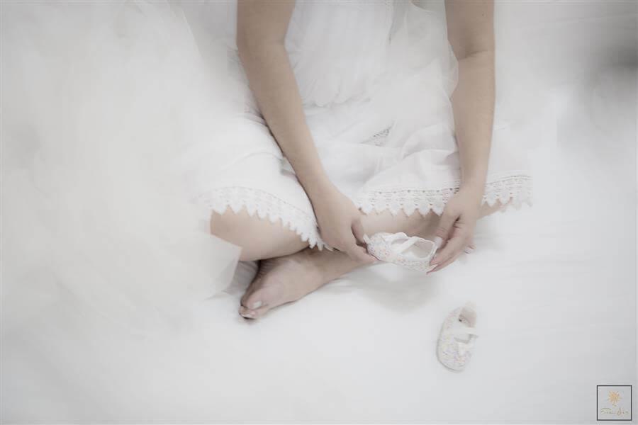Foto de grávida olhando sapatinhos de bebê durante ensaio de gestante em BH.