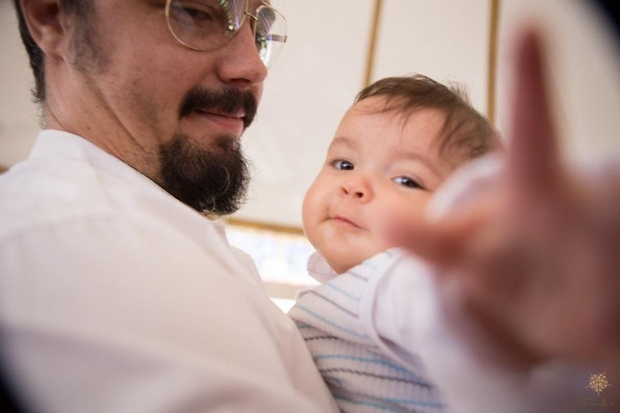Bebê nos braços do pai brincando com a câmera da fotógrafa em Batismo em BH.