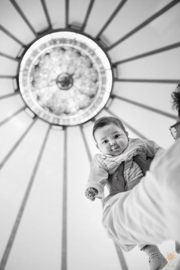 Bebê nos braços do pai, em Batismo na Igreja São Judas Tadeu em Belo Horizonte.
