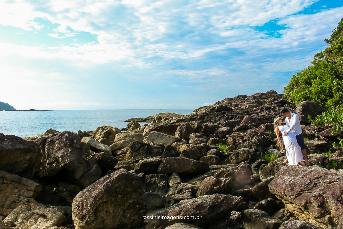 casal no ensaio fotografico na praia com pedra e o casal com roupas claras