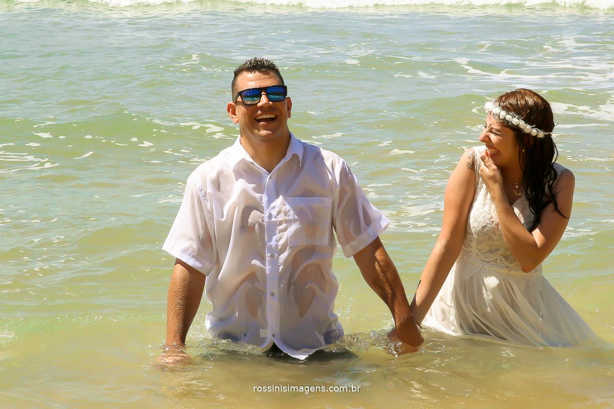 ensaio na praia casal no mar noiva rindo do noivo