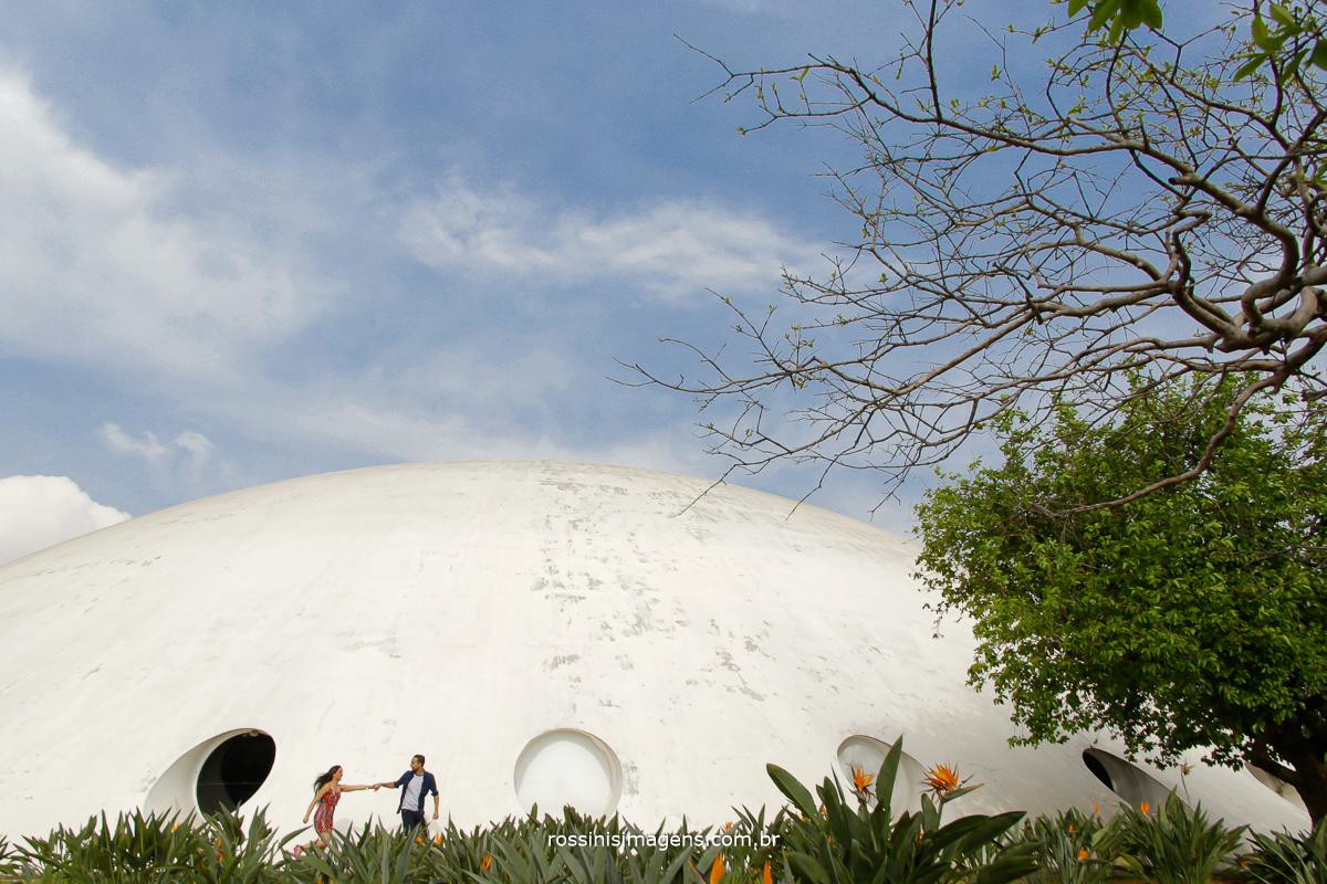 ensaio fotográfico casal no parque em são paulo noivo puxando a noiva correndo na frente da oca do parque do ibirapuera