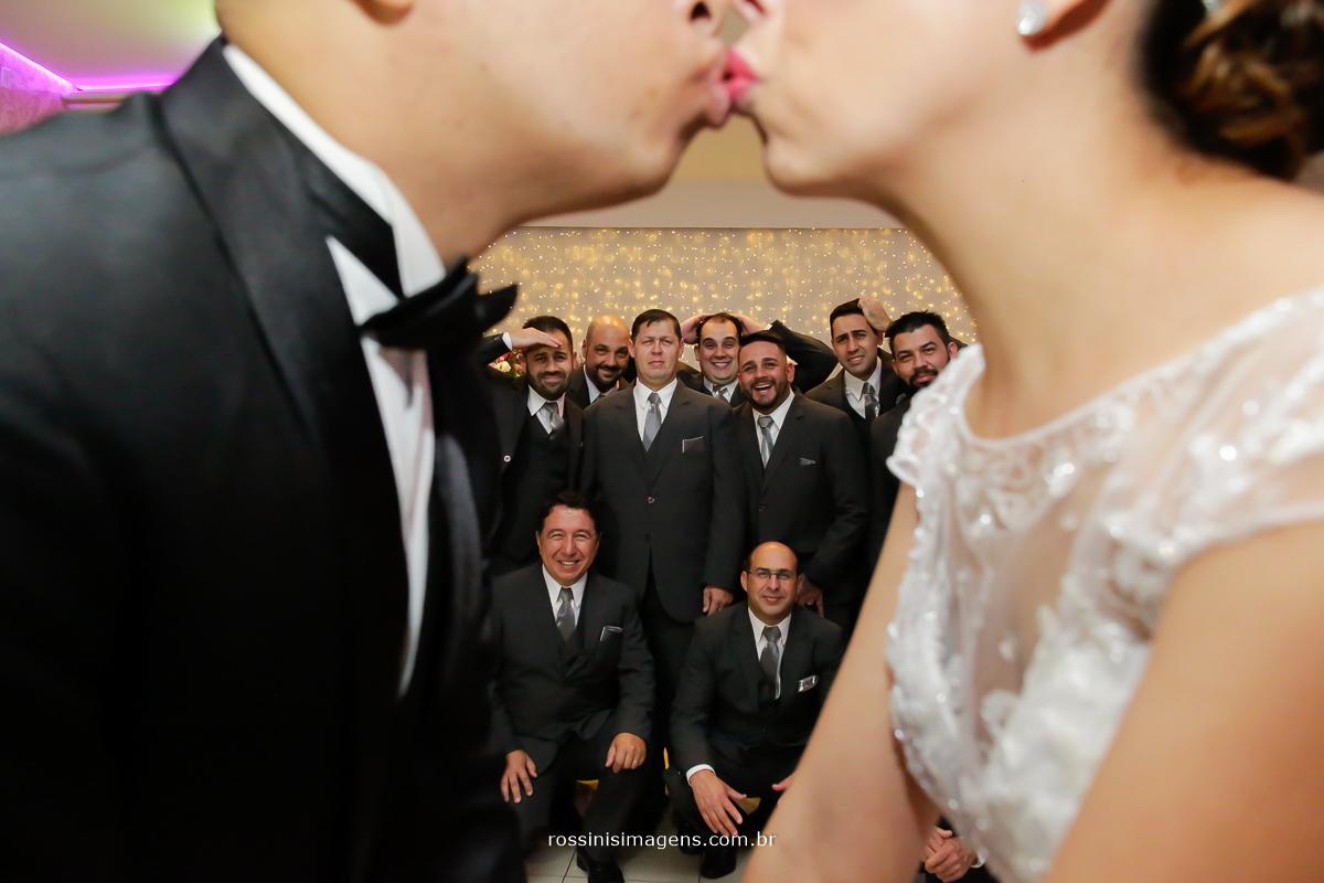 sessão de fotos noivos se beijando e madrinhas e padrinhos ao fundo