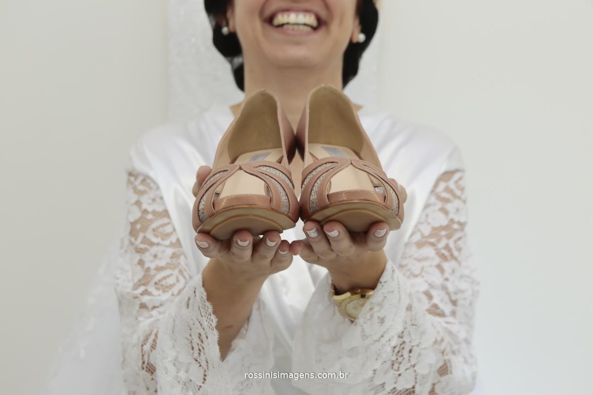 noiva feliz exibindo sapato do casamento