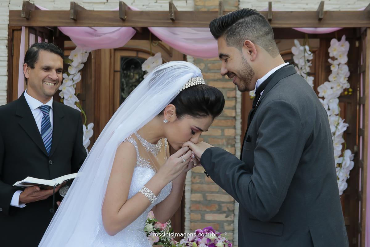noiva beijando a aliança na mão do noivo