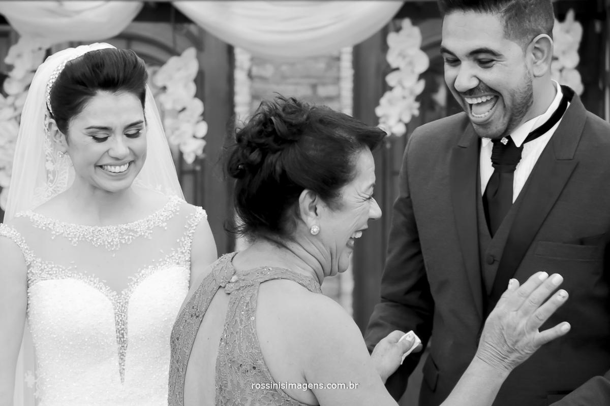 mãe da noiva dando beliscão no noivo e todos dando muito risada