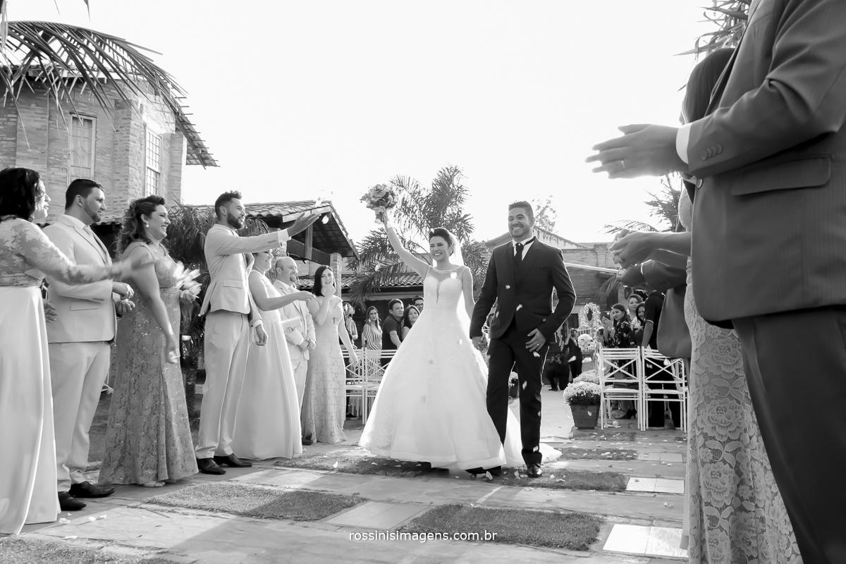 foto pb dos noivos ao final da cerimonia muito empolgados