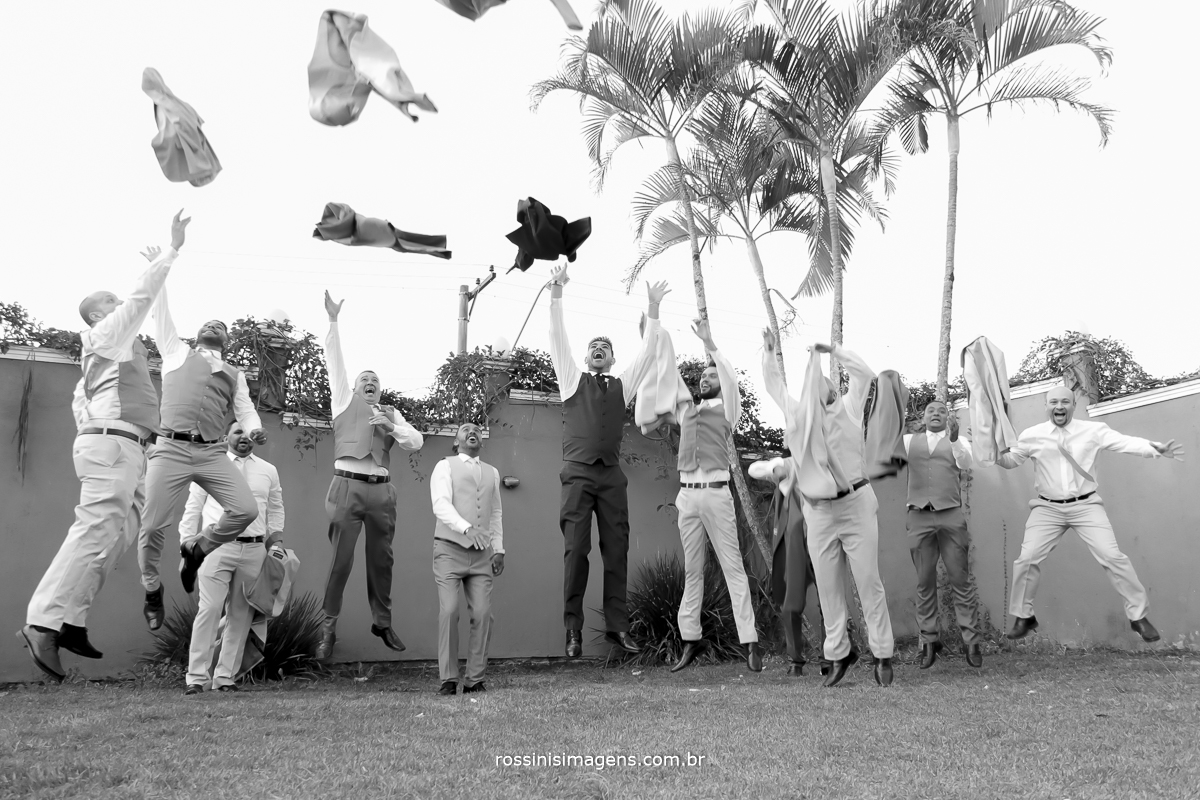 sessão de fotos com os padrinhos pulando jogando o terno para cima