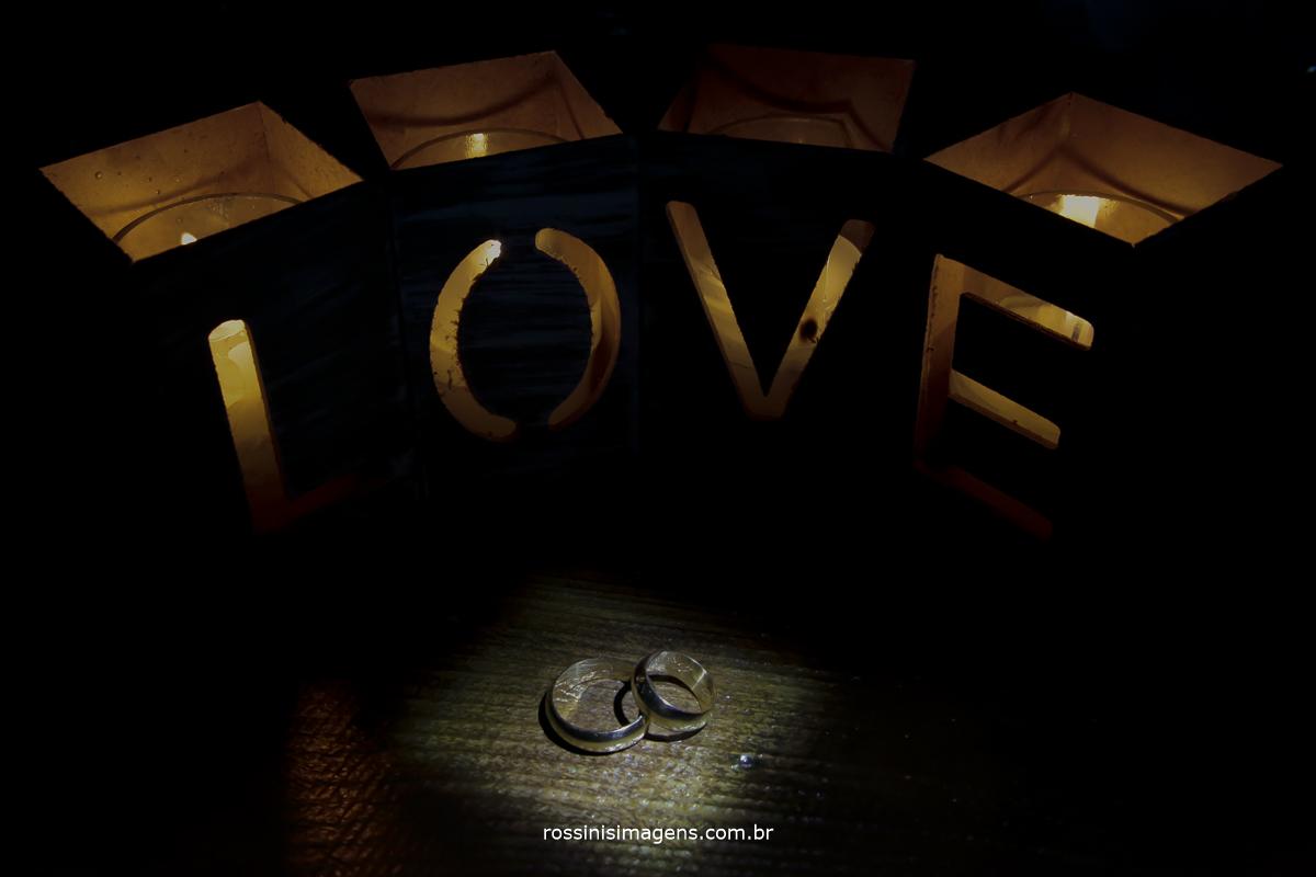fotografia de casamento as alianças com a palavra love em volta