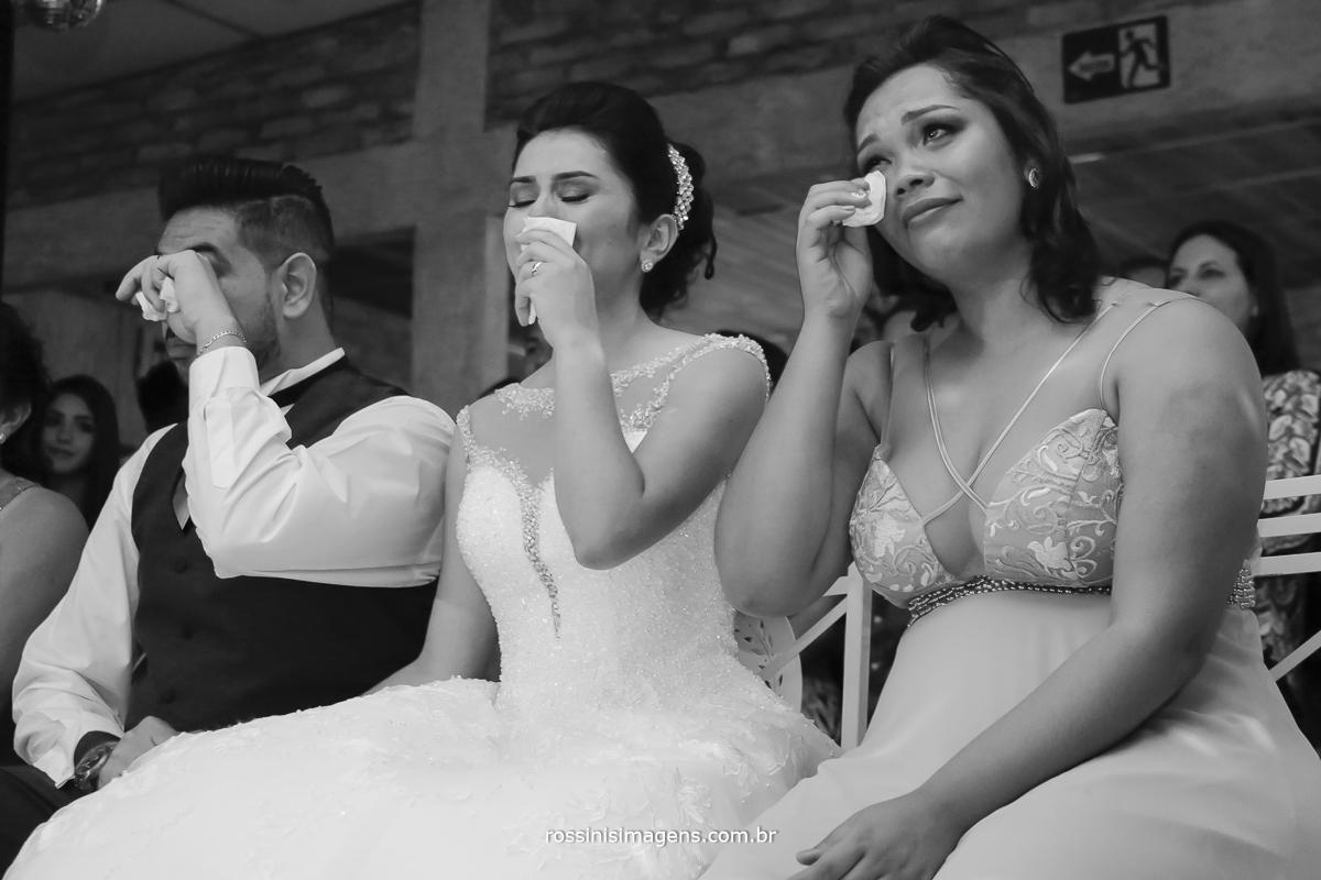 foto pb noivos emocionados assistindo retrospectiva, muita emoção