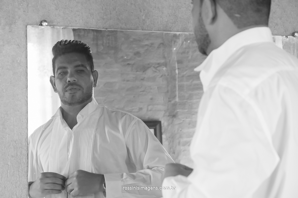 noivo fechando a camisa, toda a preparação para o casamento