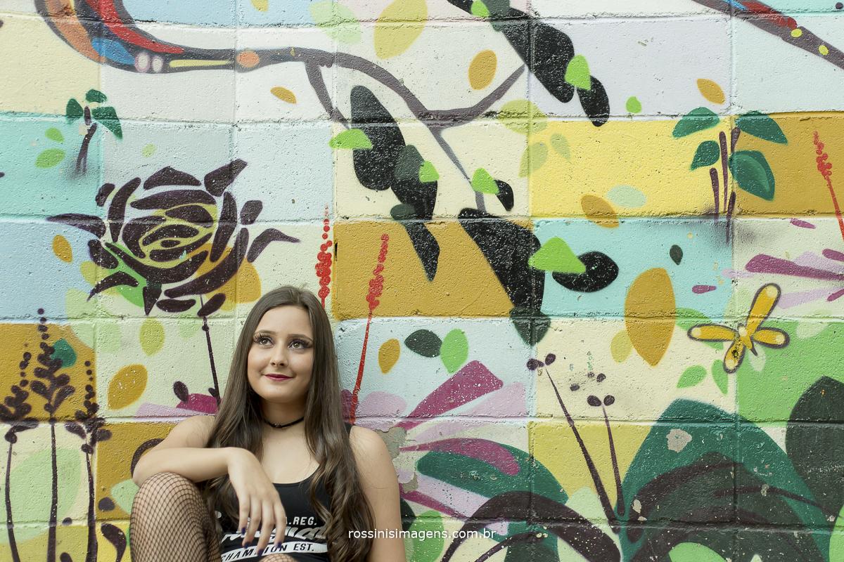 debutante sentada no chão parede de funco com grafite de flores
