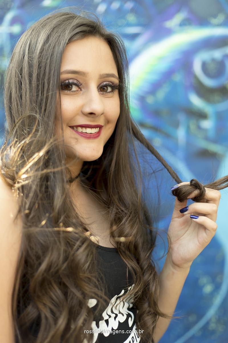 debutante enrolando cabelo na sessão de fotos para festa de 15 anos