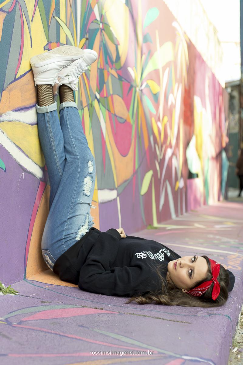 fotografo de debutante, debutante com as pernas na parede calça jeans e tiara vermelha na cabeça