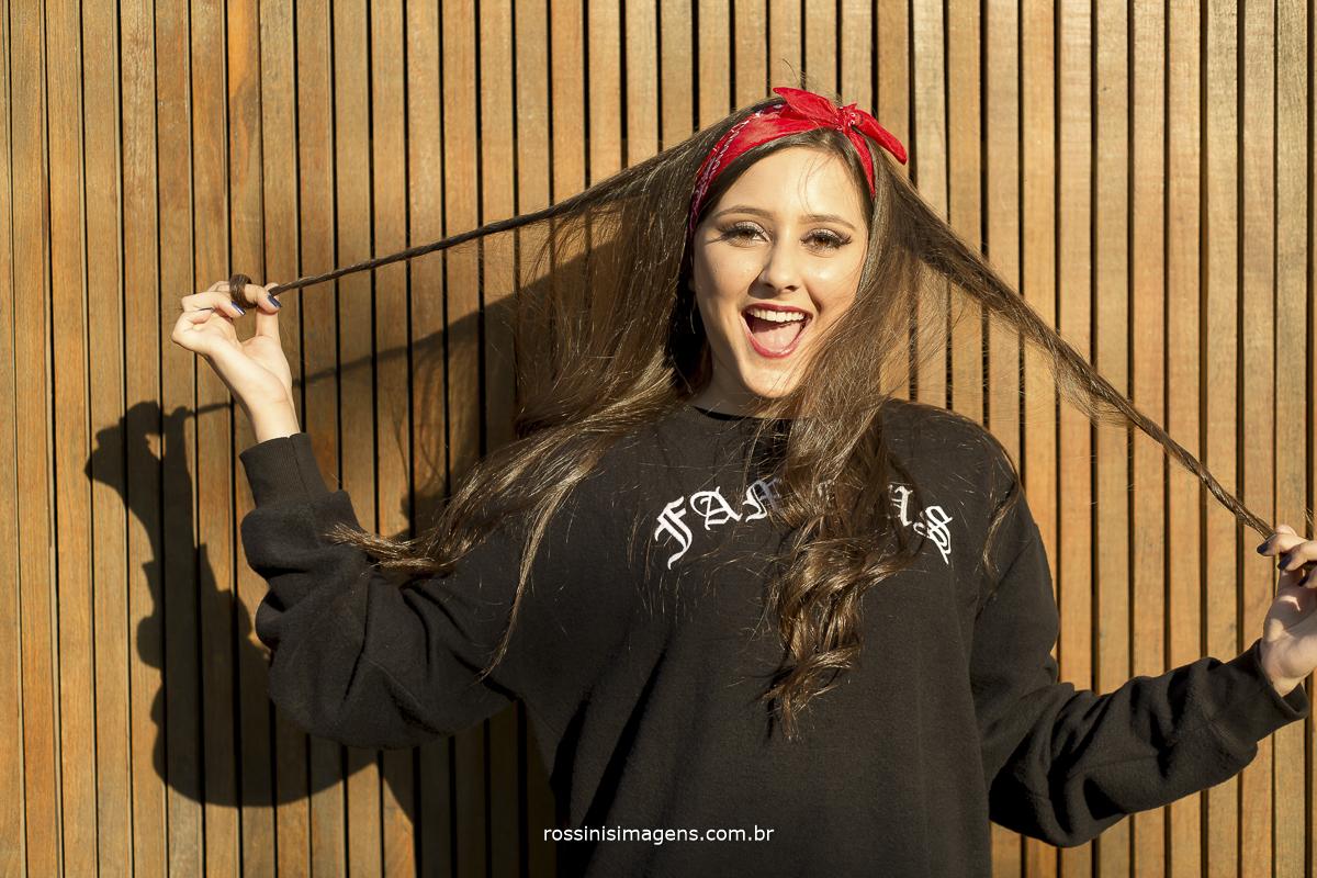 sessão fotográfica da isabella no beco, debutante mexendo nos cabelos e sorrindo