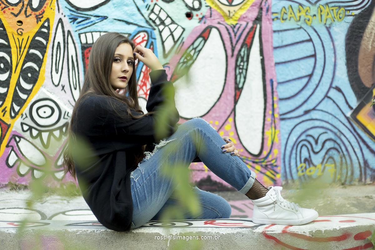 parede colorida na sessão externa da debutante Isa sentada e pensando