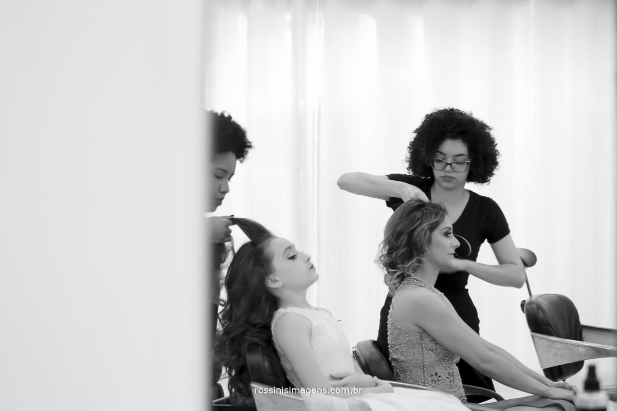 cabeleireira preparando o penteado da mãe e irmã da debutante isabella