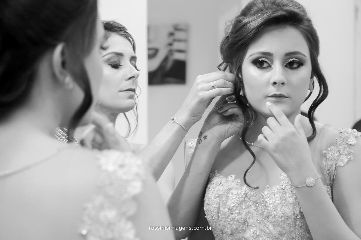 debutante isabella colocando brinco em frente ao espelho com a ajuda de sua mãe