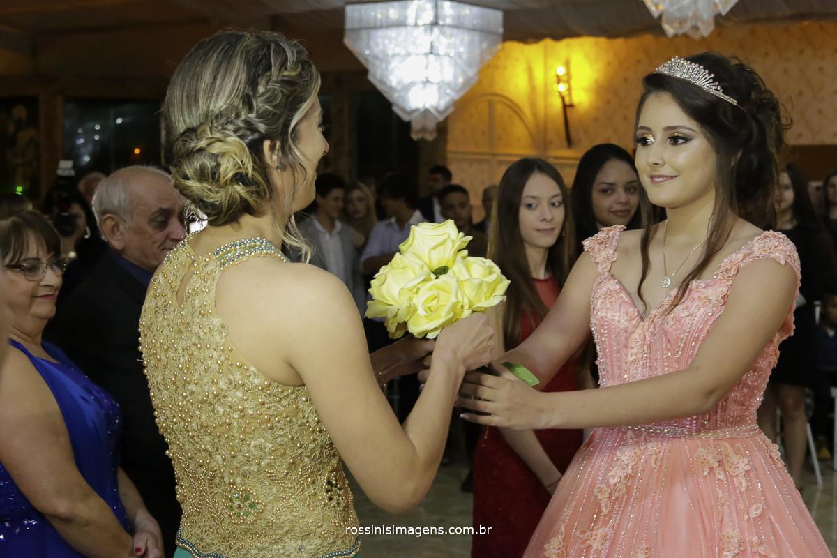 debutante entregando um buquê de flores para sua mãe durante o cerimonial
