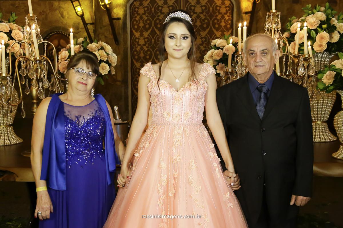 fotos da debutante isabella na mesa do bolo com os avos maternos