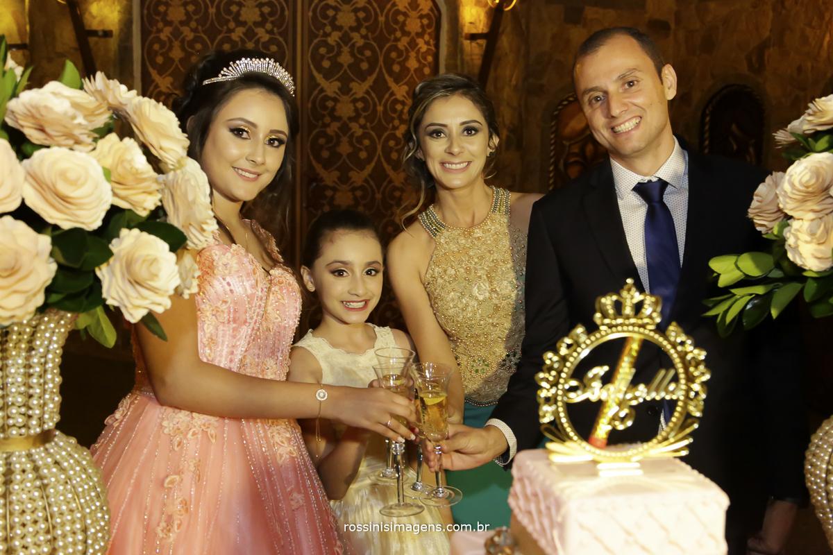 brinde da debutante com a familia na mesa do bolo