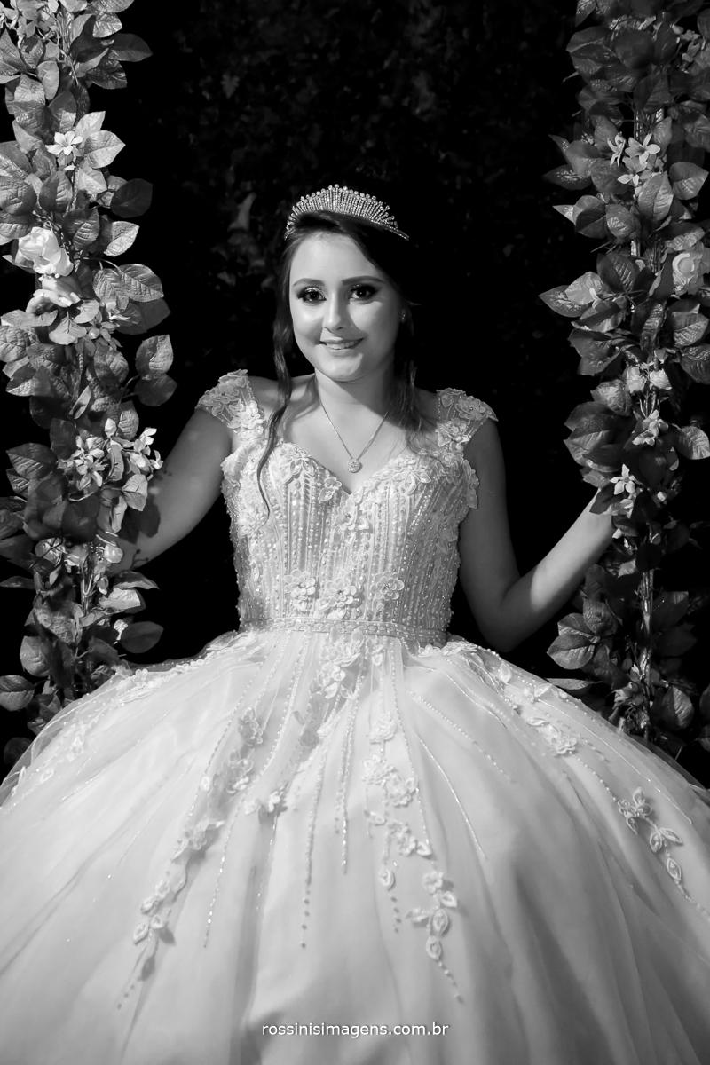 debutante sorrindo na balança de flores no castelo na sessão de fotos