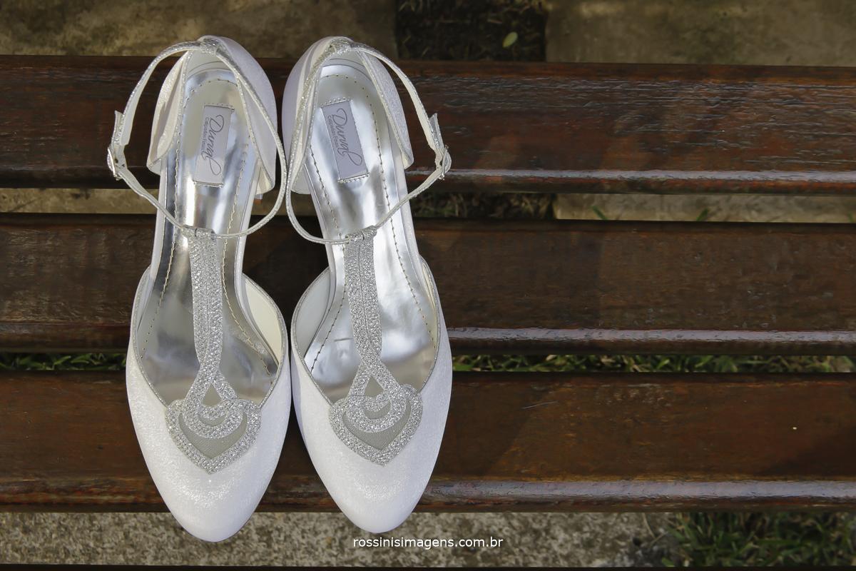 sapato branco da noiva em cima do banco de madeira