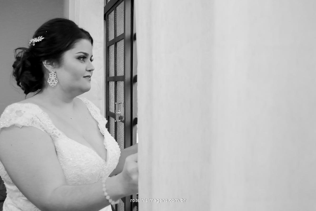 noiva abrindo a cortina e olhando pela janela no grande dia, dia do casamento