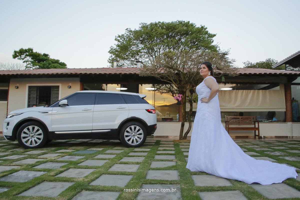 noiva no making of pronta com vestido e o carro Land Rover