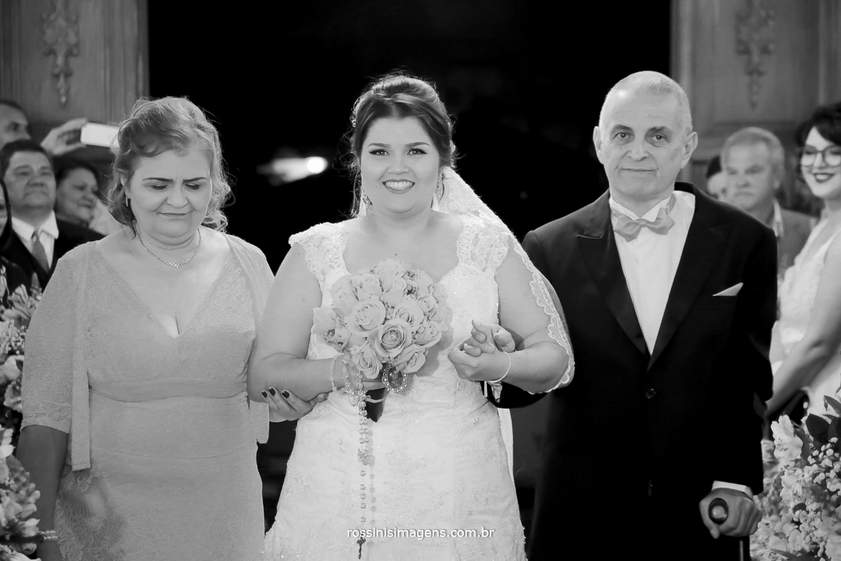 a linda entrada da noiva com os pais em direção ao altar