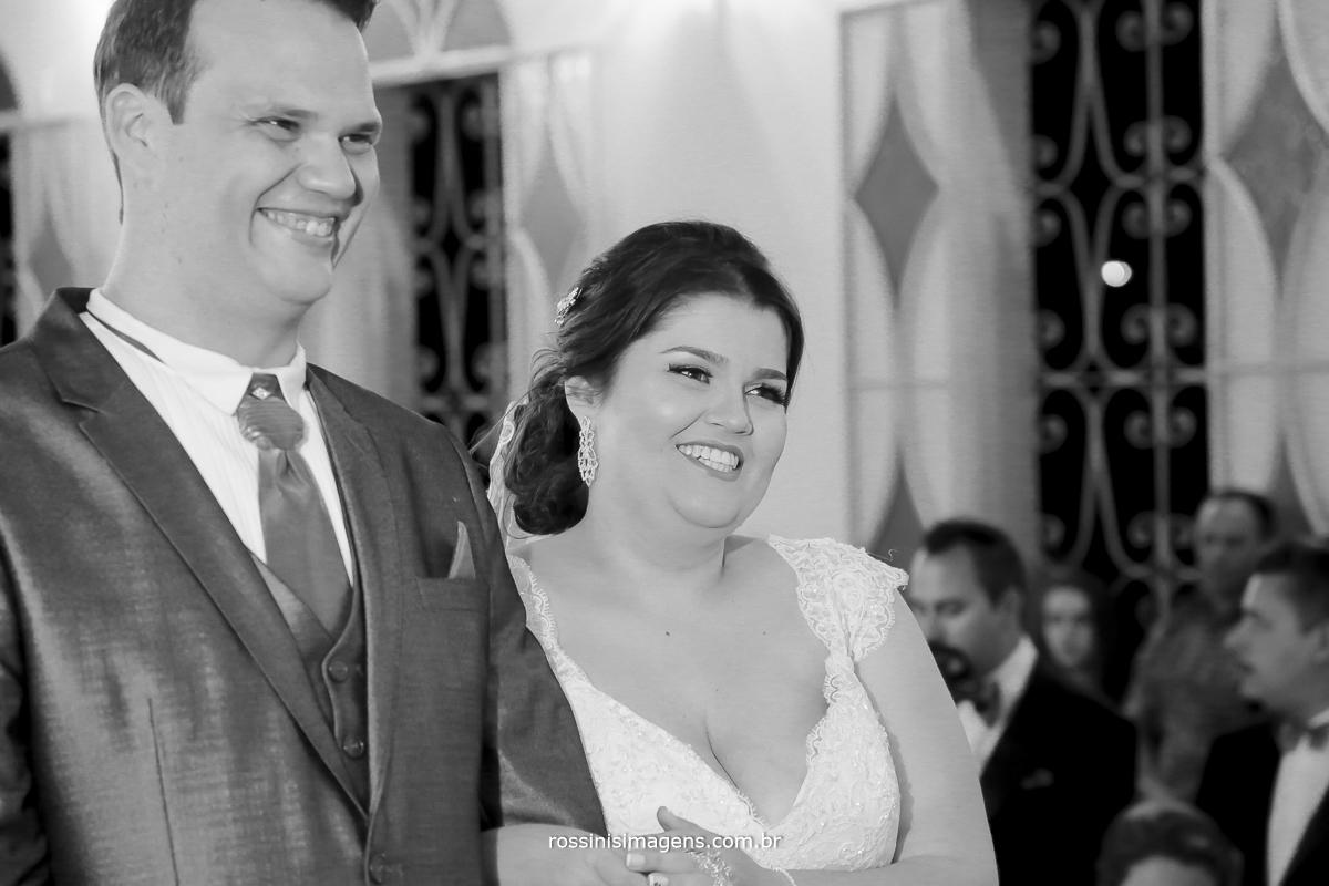 casal sorrindo para o padre celebrando o casamento