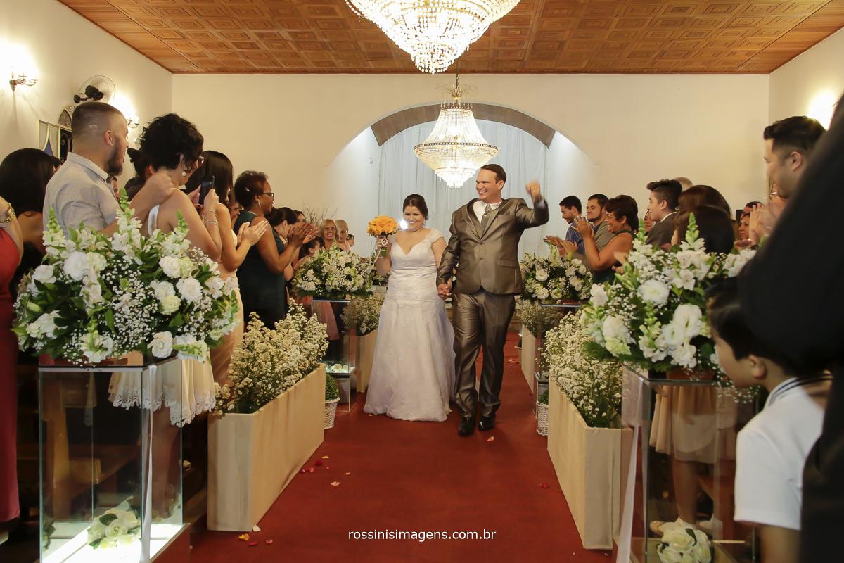 foto de frente da saida dos noivos depois da cerimonia muita energia e animação