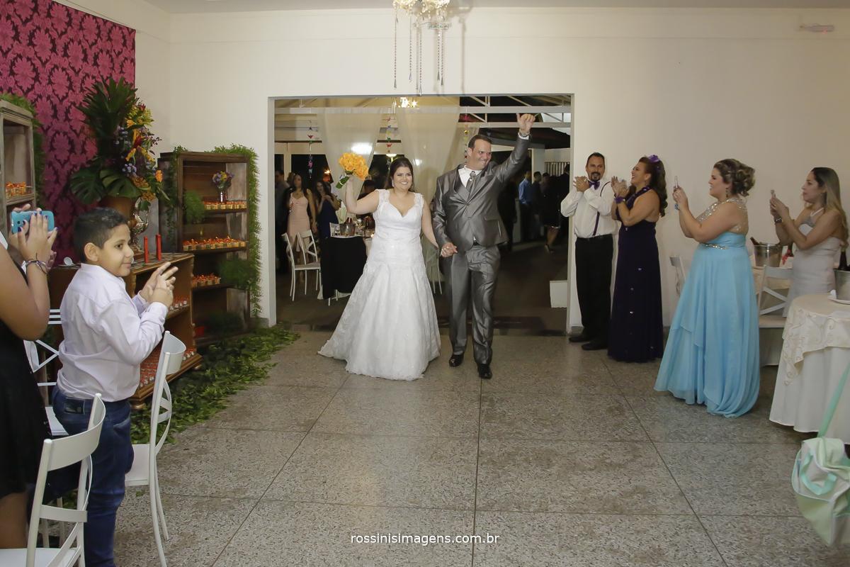 entrada dos noivos na recepção agitando a festa