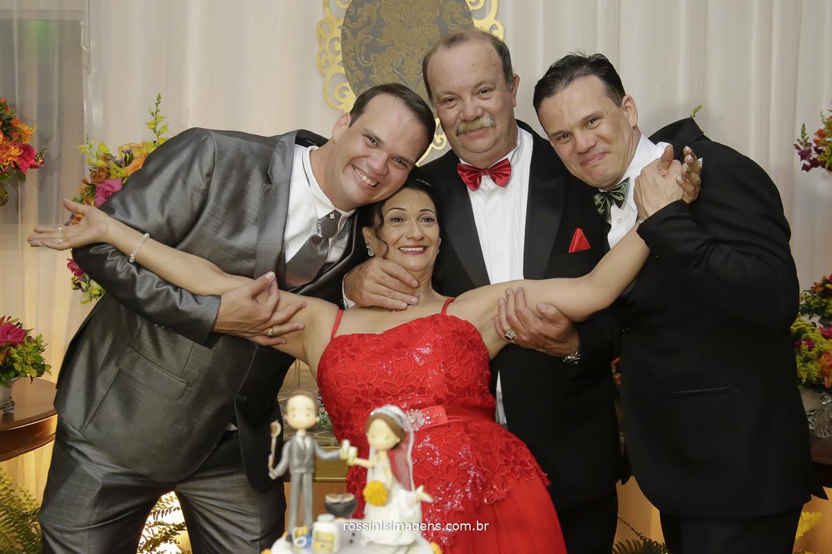noivo com sua mae, pai e irmão na mesa do bolo para a foto de familia