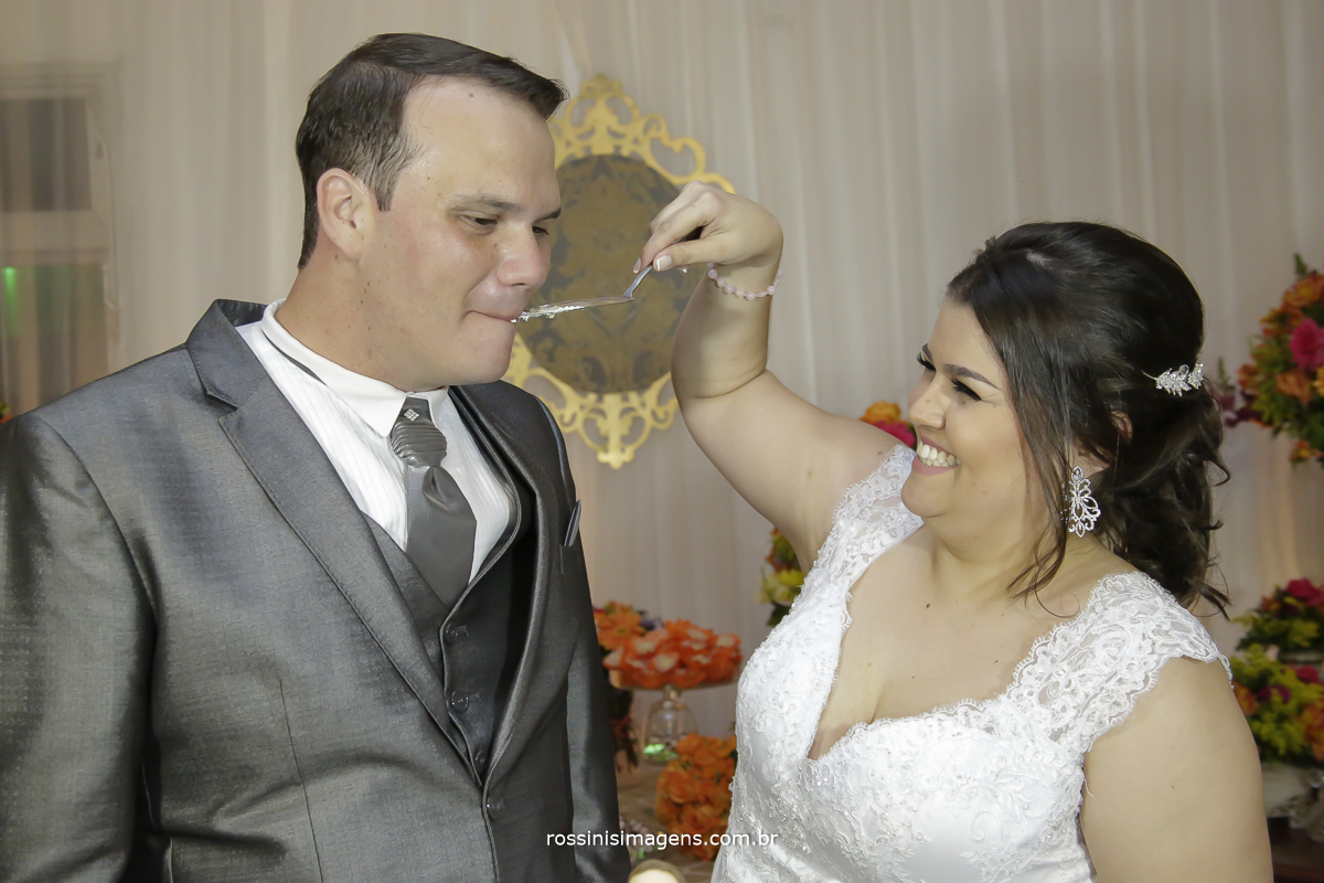 fotografia espontânea da noiva dando bolo ao noivo, muito feliz