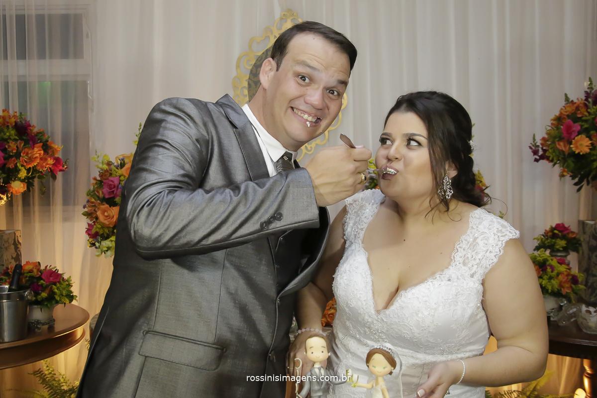 noivo retribuindo a gentileza da noiva dando um pedaço do bolo, animado