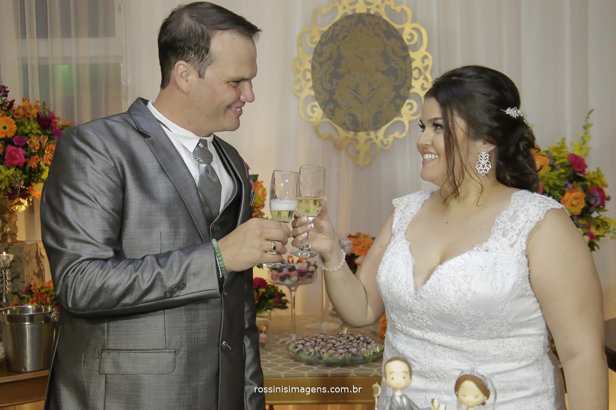 fotografia protocolar do brinde dos noivos diferente  na mesa do bolo