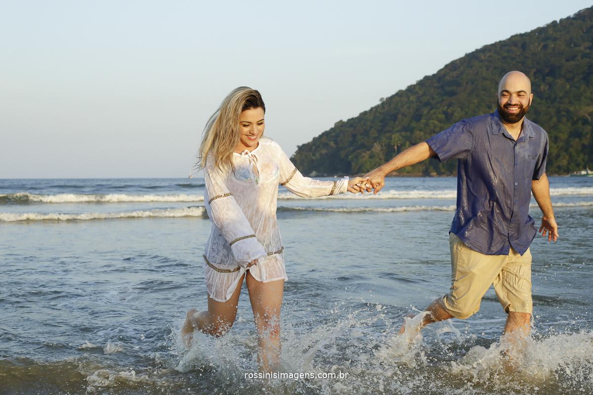 casal correndo no mar felizes e alegres com por do sol na praia no ensaio pré-casamento
