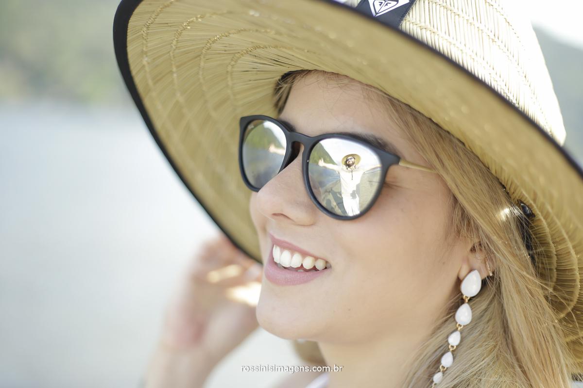 noivo no reflexo do óculos da noiva na praia